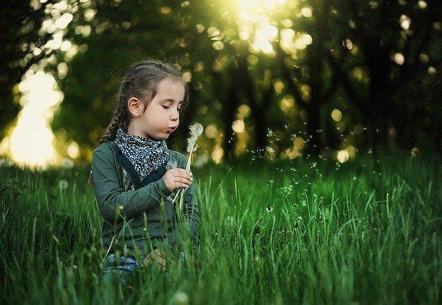 santé enfants topophilie - une petite fille qui souffle un pissenlit